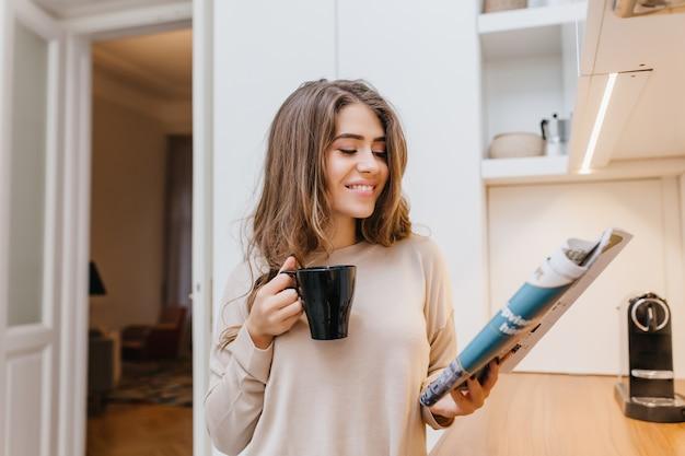 Atrakcyjna dziewczyna w modnej koszuli czytania magazynu z zainteresowaniem