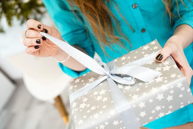 Atrakcyjna dziewczyna w niebieskiej koszuli otwiera prezent - zbliżenie zdjęcia