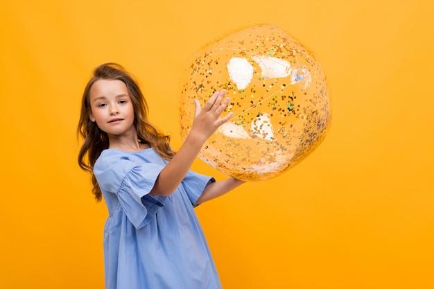 Atrakcyjna dziewczyna w niebieskiej sukience trzyma błyszczącą przezroczystą piłkę na żółtym tle