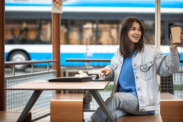 Atrakcyjna dziewczyna w niezobowiązującym stylu pije kawę na letnim tarasie i czeka na kogoś