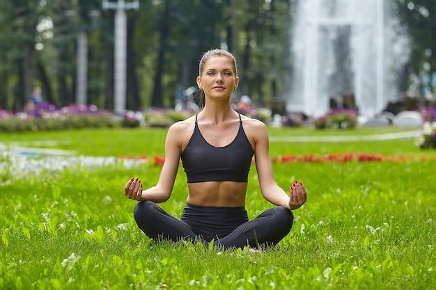 Atrakcyjna dziewczyna w odzieży sportowej robi ćwiczenia gimnastyczne na trawie w mieście w parku miejskim.