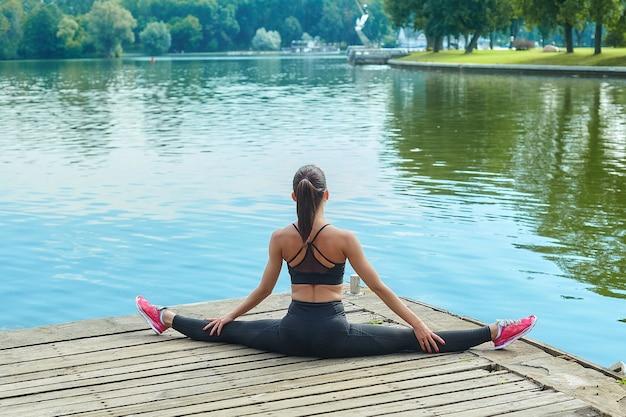 Atrakcyjna dziewczyna w odzieży sportowej wykonuje ćwiczenia gimnastyczne na drewnianym molo w parku miejskim.