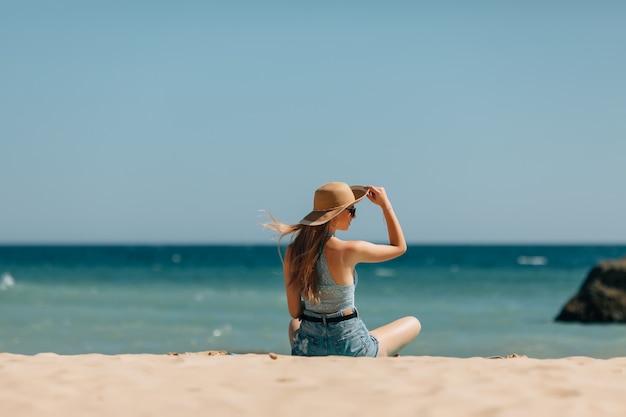 Atrakcyjna dziewczyna w okularach przeciwsłonecznych i kapeluszu leży na ciepłym piasku