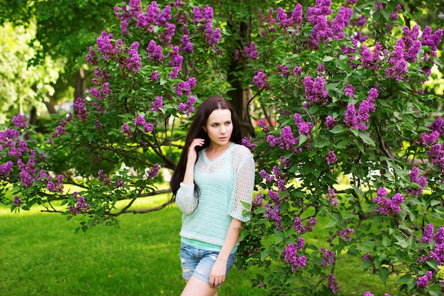 Atrakcyjna dziewczyna w parku przed kwitnącym drzewem. portret kobiety.