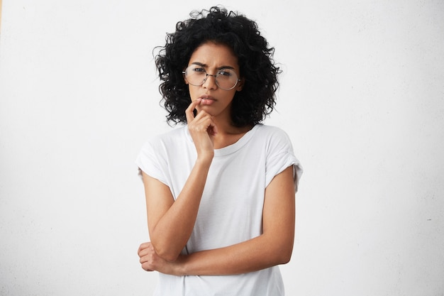 Atrakcyjna dziewczyna w przypadkowej koszulce i okrągłych okularach ściskając oczy i trzymając rękę na brodzie