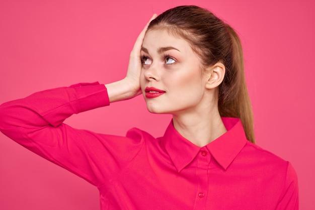 Atrakcyjna dziewczyna w różowej koszuli przycięty widok jasny makijaż czerwone usta gestykuluje rękami kopia przestrzeń.