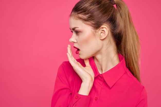 Atrakcyjna dziewczyna w różowej koszuli przycięty widok jasny makijaż czerwone usta gestykuluje rękami