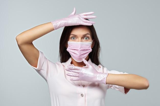 Atrakcyjna dziewczyna w różowych rękawiczkach i masce ochronnej
