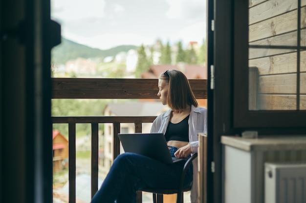 Atrakcyjna dziewczyna w stylowe ubranie pracuje na laptopie na balkonie w mieszkaniu