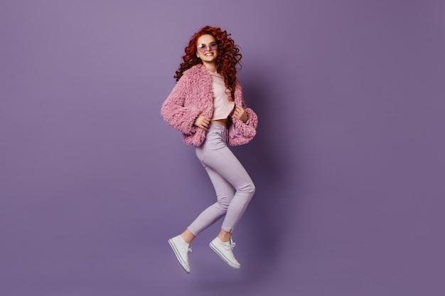 Atrakcyjna dziewczyna w stylowych obcisłych spodniach, białej koszulce i różowym płaszczu skacze na liliowej przestrzeni.