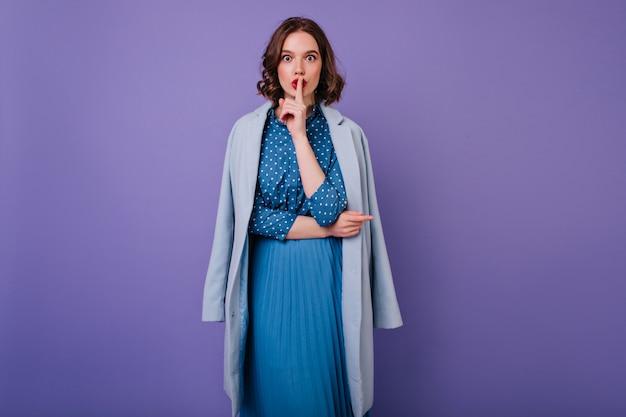 Atrakcyjna dziewczyna w sukienka vintage z fioletową ścianą. wewnętrzne zdjęcie inspirowanej kręconej kobiety w niebieskim płaszczu pragnie ciszy.