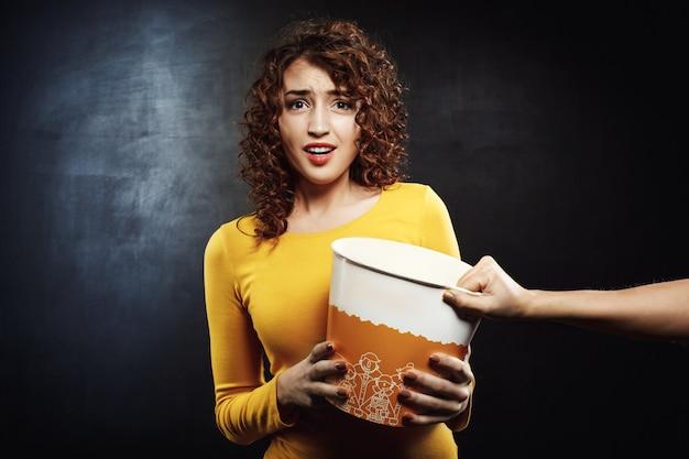 Atrakcyjna dziewczyna wygląda smutno, dążąc do wiadra popcornu z przyjacielem