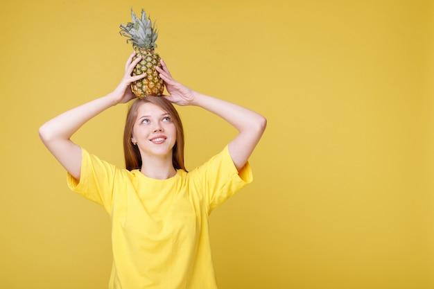 Atrakcyjna dziewczyna z ananasem na żółtej ścianie