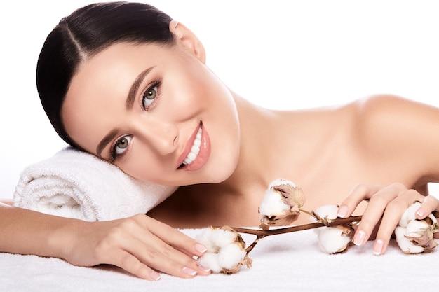 Atrakcyjna dziewczyna z brązowymi włosami związanymi z tyłu, czystą, świeżą skórą, dużymi oczami i nagimi ramionami z kwiatem i ręcznikiem na białej ścianie, z bliska.