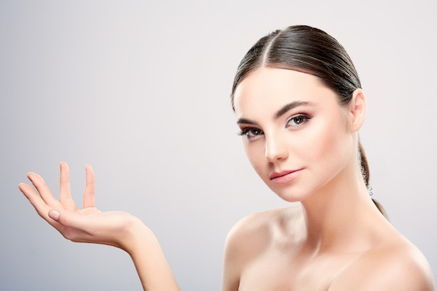 Atrakcyjna dziewczyna z ciemnobrązowymi włosami związanymi z tyłu, dużymi oczami, ciemnymi brwiami i nagimi ramionami patrząc w kamerę, modelka z jasnym makijażem nude, trzymająca produkt, makieta.