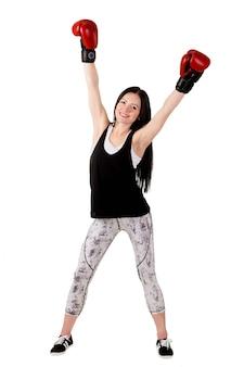 Atrakcyjna dziewczyna z długimi włosami podniosła ręce w czerwonych rękawicach bokserskich.