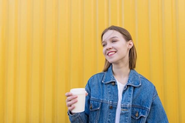 Atrakcyjna dziewczyna z filiżanką kawy w dłoniach stoi na tle żółtej ściany i uśmiecha się.