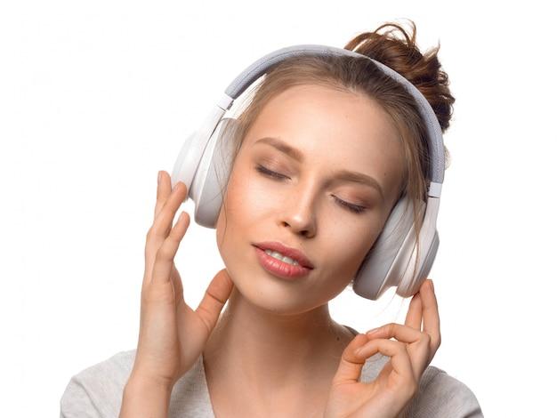 Atrakcyjna dziewczyna z hełmofonami na biel ścianie
