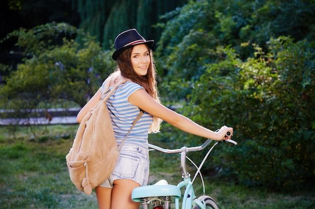 Atrakcyjna dziewczyna z kręconymi włosami na sobie kapelusz, top i spodenki stojąc z rowerem w parku, podróże, portret, lato zdjęcie.