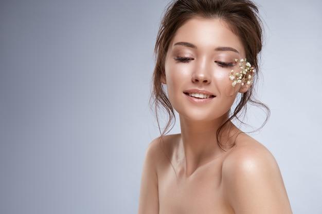 Atrakcyjna dziewczyna z kwiatami na jej policzku, uśmiechając się i patrząc w dół