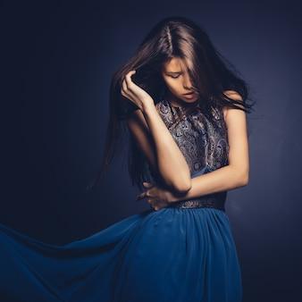 Atrakcyjna dziewczyna z latającym włosy pozuje w studiu