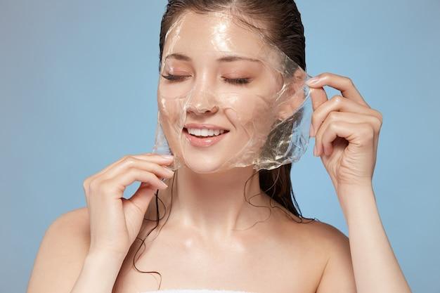 Atrakcyjna dziewczyna z nagimi ramionami i mokrymi włosami, zdejmując maseczkę z zamkniętymi oczami