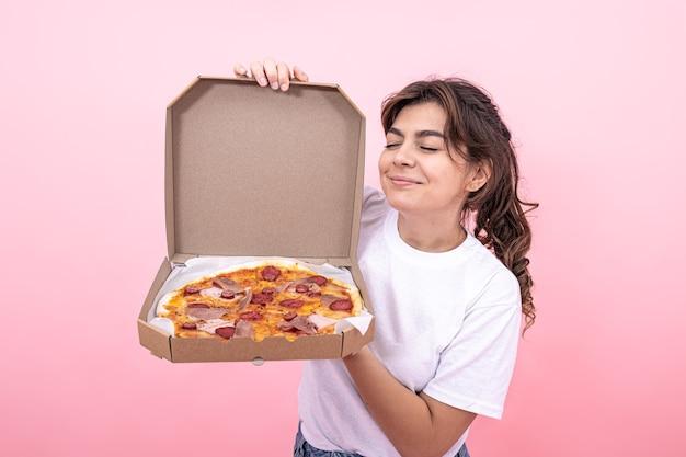 Atrakcyjna dziewczyna z otwartym pudełkiem pizzy na różowym tle