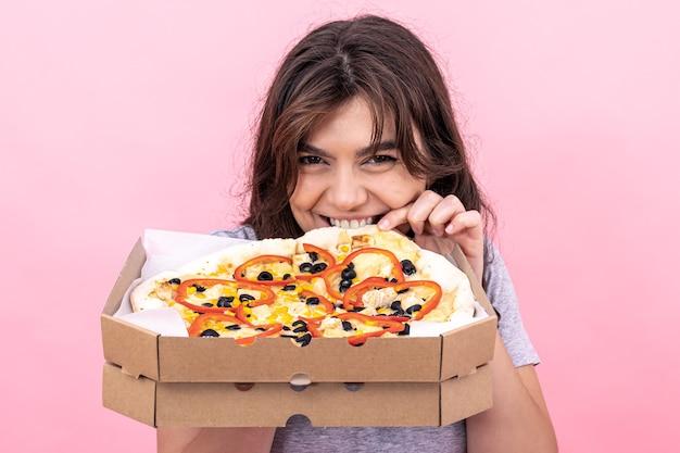 Atrakcyjna dziewczyna z pizzą w pudełku do dostawy na różowym tle