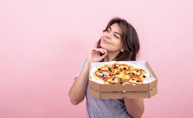 Atrakcyjna dziewczyna z pizzą w pudełku z dostawą na różowym tle.