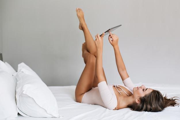 Atrakcyjna dziewczyna z tabletem na łóżku w nowoczesnym mieszkaniu rano. trzyma w górze niegrzeczne nogi, wygląda na zadowoloną.