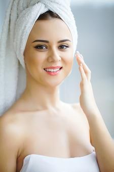 Atrakcyjna dziewczyna za pomocą kremu do skóry