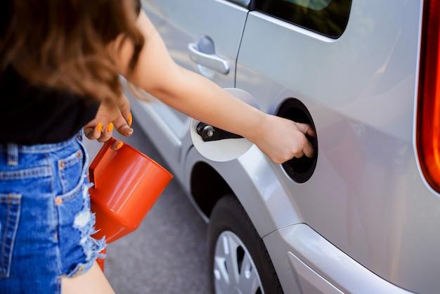 Atrakcyjna dziewczyna zapełni zbiornik nowoczesnego samochodu