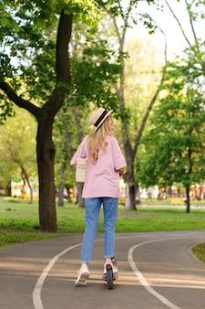 Atrakcyjna dziewczyna ze skuterem w parku miejskim latem