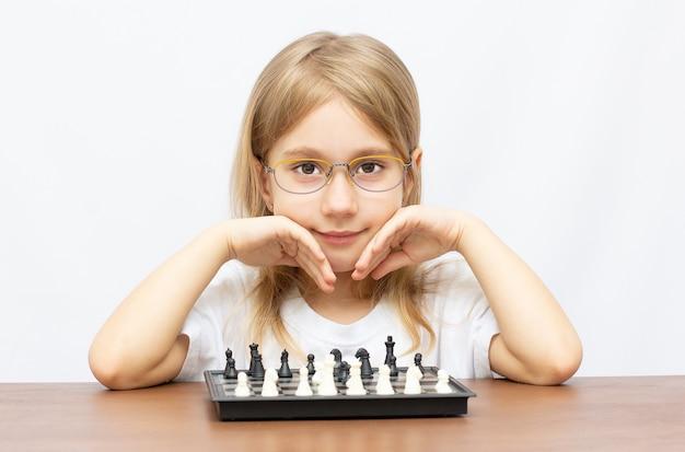 Atrakcyjna dziewczynka gra w szachy na białym tle