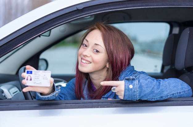 Atrakcyjna dziewczynka kaukaski siedzi w samochodzie posiadania prawa jazdy