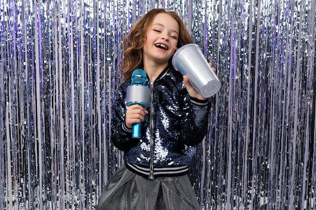 Atrakcyjna dziewczynka kaukaski w konkursie talentów z mikrofonem i szklanką napoju na błyszczącym tle.