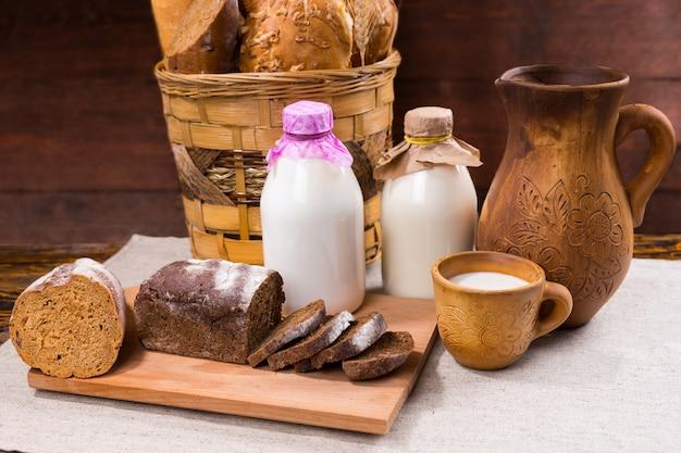 Atrakcyjna ekspozycja rustykalnego pieczywa w plecionym koszu dzbanek i kubek mleka oraz pół pokrojony bochenek pumpernikla na desce do krojenia