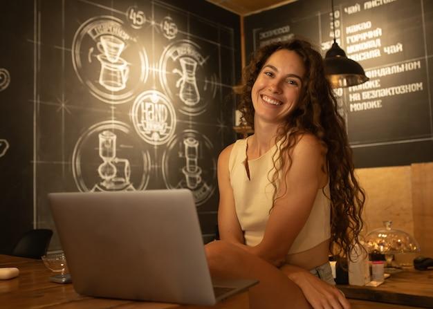 Atrakcyjna elegancka brunetka kobieta z kręconymi włosami siedzi w kawiarni, ciesząc się kawą