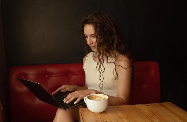 Atrakcyjna elegancka brunetka siedzi w kawiarni, ciesząc się kawą i za pomocą laptopa