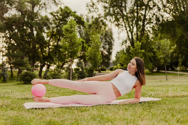 Atrakcyjna, elegancka kobieta jest zaangażowana w pilates z piłką na zielonej trawie trawnika o zachodzie słońca.
