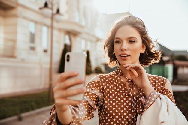 Atrakcyjna elegancka kobieta trzyma smartfon i robi selfie. niesamowita europejska dama w brązowej sukience pozuje na ulicy.