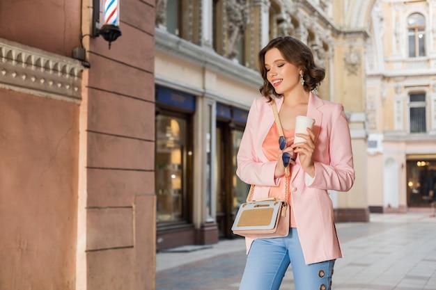 Atrakcyjna elegancka kobieta w stylowym stroju spacery po mieście, moda uliczna, trend wiosenno-letni, uśmiechnięty szczęśliwy nastrój, ubrana w różową kurtkę i bluzkę, akcesoria, fashionistka na zakupy we włoszech