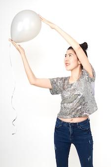Atrakcyjna elegancka piękna azjatykcia kobieta z pastelowymi balonami na białych tło