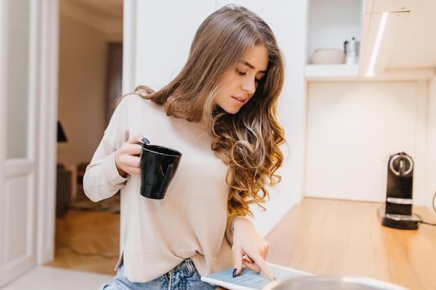 Atrakcyjna europejka z kręconymi fryzurami czyta magazyn w swoim pokoju