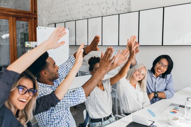 Atrakcyjna europejska kobieta macha rękami z przyjaciółmi, szczęśliwa z udanego spotkania. afrykańscy i azjatyccy pracownicy biurowi bawią się podczas konferencji i śmieją się.