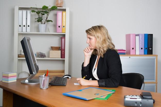Atrakcyjna fachowa kobieta pracuje przy jej biurowym biurkiem