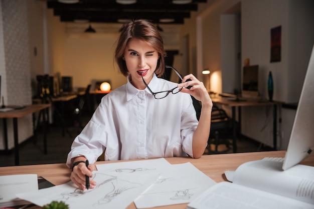 Atrakcyjna figlarna młoda kobieta projektantka mody trzymająca okulary i mrugająca w biurze