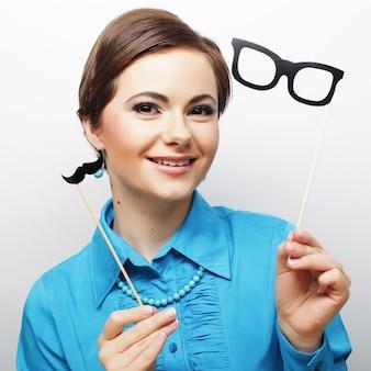 Atrakcyjna figlarna młoda kobieta trzyma wąsy i okulary na patyku. gotowy na imprezę.