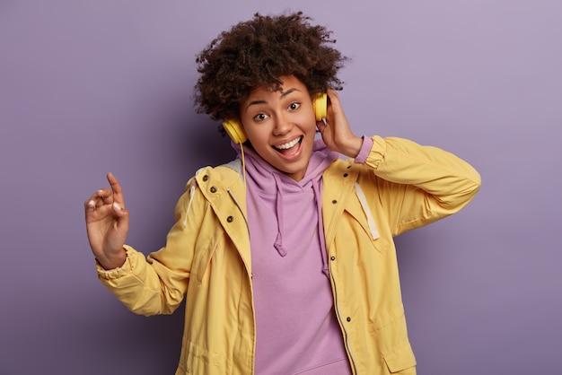Atrakcyjna, figlarna, szczęśliwa nastolatka śpiewa do muzyki