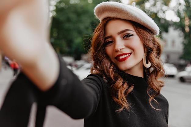 Atrakcyjna francuska dziewczyna z rudymi włosami pozuje w listopadowy dzień. zewnątrz strzał eleganckiej kaukaskiej damy z czerwonymi ustami, robiąc selfie na ścianie ulicy.